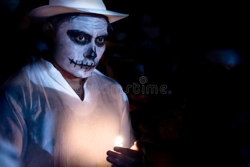 Weißer customed Mann mit dem Schädelmake-up und weißem Hut, die eine Kerze an der Parade für Dias de Los Muertos am Festival-DES  stockfoto
