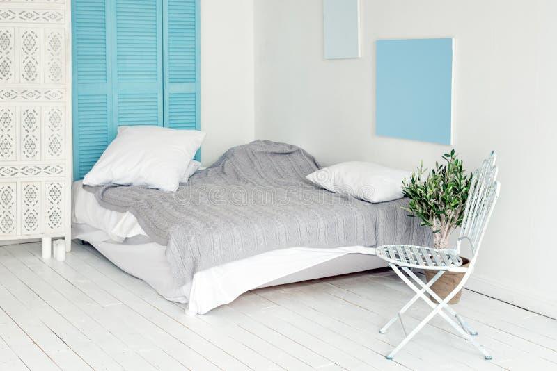 Weißer Dachbodeninnenraum in der skandinavischen Art Gemütlicher Bereich der Wohnung in der nordischen Art, Schlafzimmer mit weiß stockbild