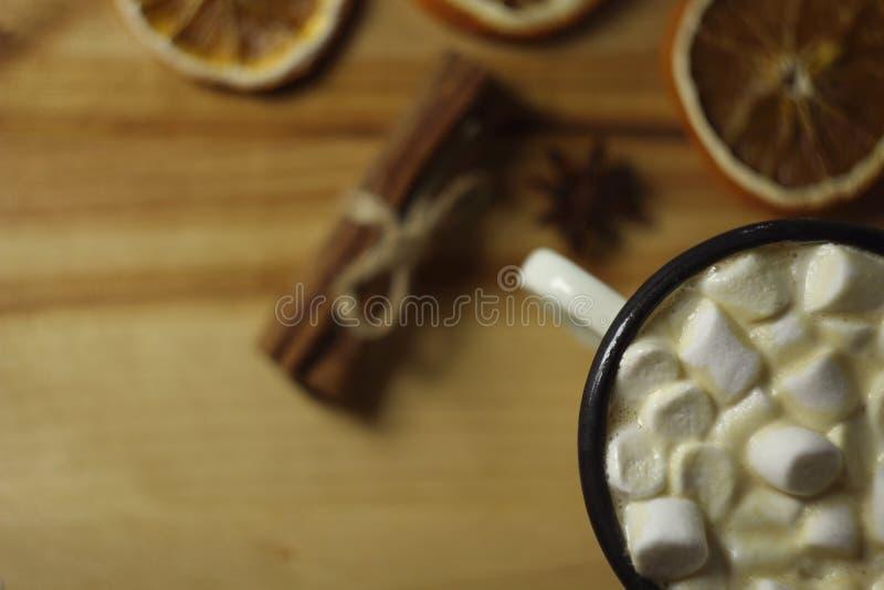 Weißer Eibisch im weißen runden Becher auf altem Holztisch mit Zimt, getrockneten Orangen und Sternanissamen Abschluss oben lizenzfreies stockfoto
