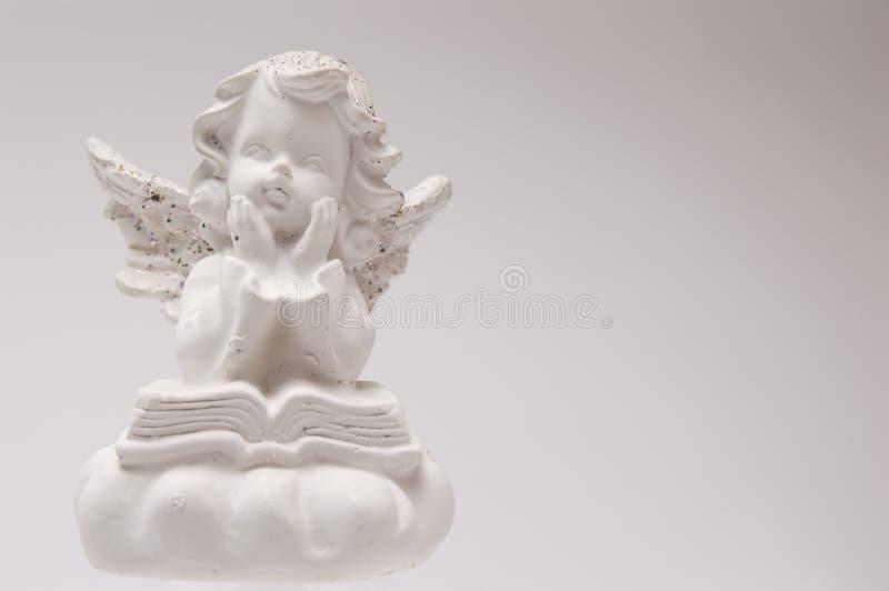 Weißer Engel des Gipses auf einer weißen Hintergrundlesung ein Buch und ein Denken lizenzfreie stockfotos