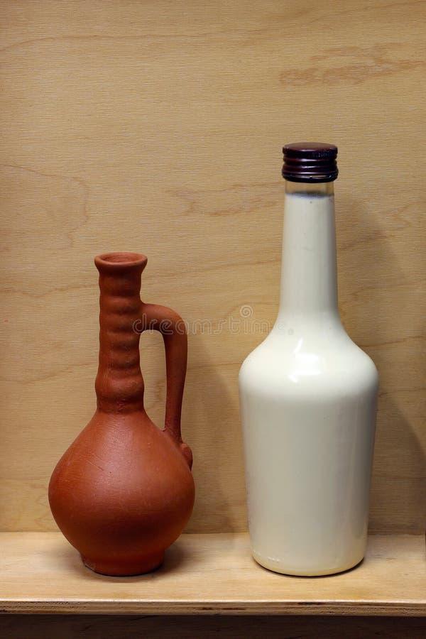 Weißer Flaschen- und Lehmbraunkrug auf einem hölzernen Regal stockfotografie