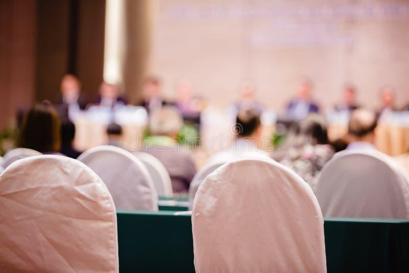 Weißer Gewebestuhl mit undeutlichem des Auditoriums für Aktionäre 'Sitzung stockfotografie