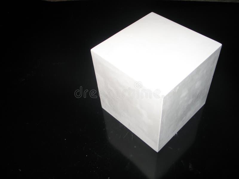 Weißer Gipswürfel auf einem schwarzen Hintergrund lizenzfreie stockfotografie