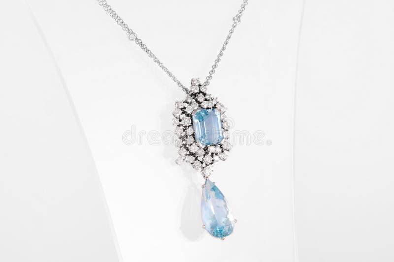 Weißer goldener Luxusanhänger mit blauem Edelstein und Diamanten auf Stand lizenzfreies stockbild