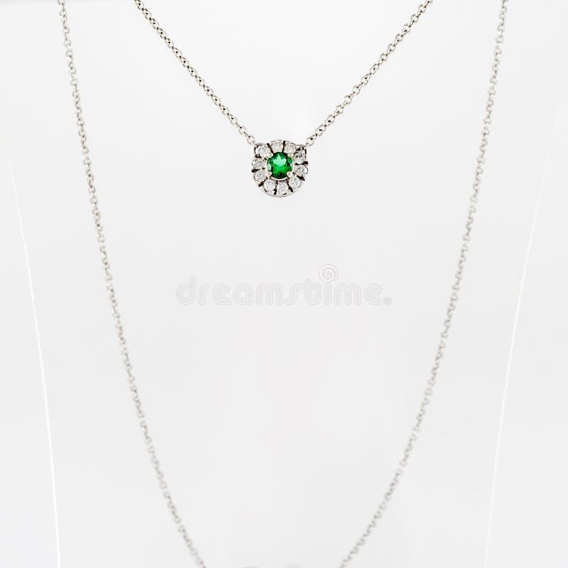 Weißer goldener Luxusanhänger mit grünem Edelstein und Diamanten auf Stand lizenzfreie stockbilder
