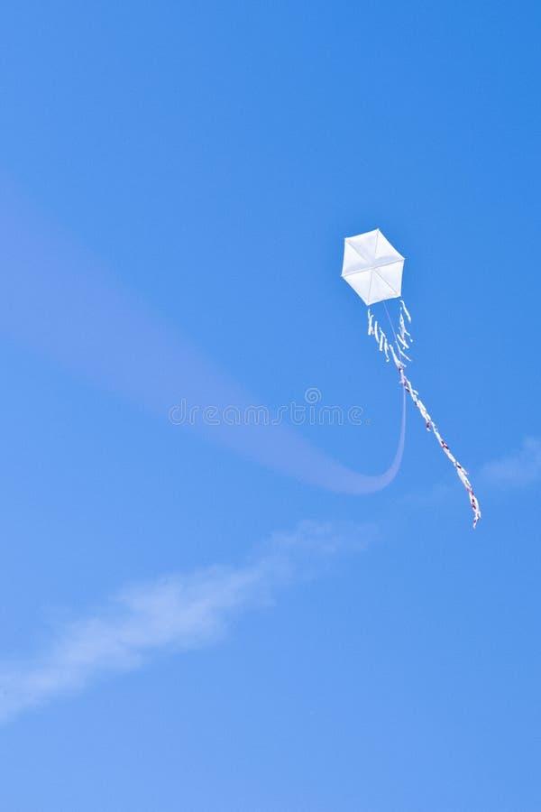 Weißer Hängegleiter an einem blauen Himmel und an den Wolken stockfoto