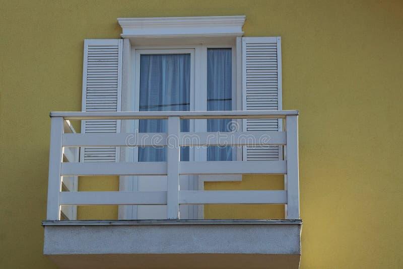 Weißer hölzerner Balkon von Planken mit einem Fenster und einer Tür auf der gelben Wand stockfotos