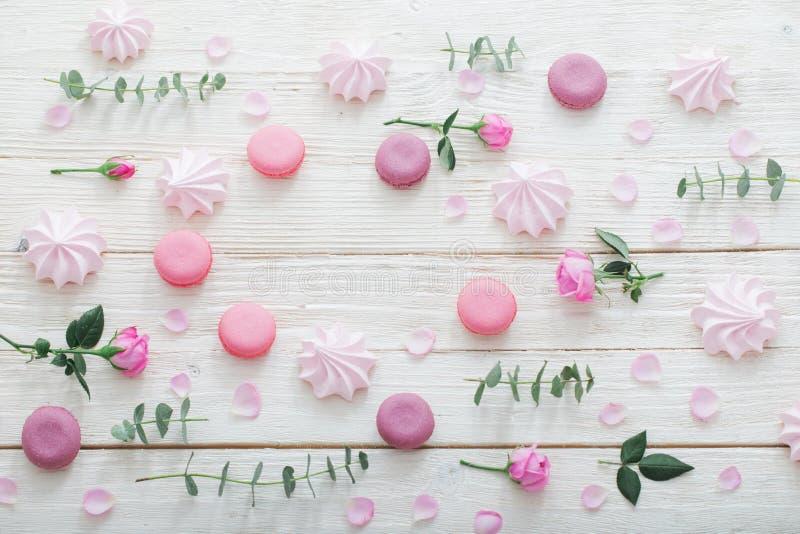 Weißer hölzerner Hintergrund mit Blumen, Makronen und Blättern stockfotografie