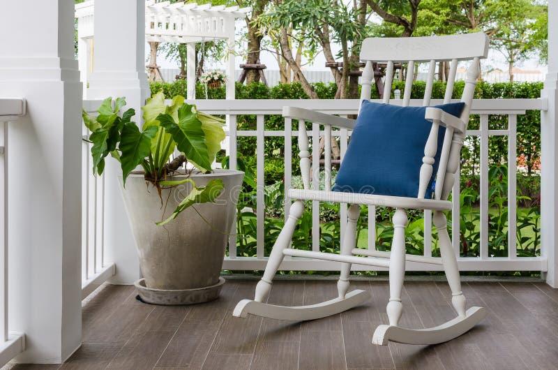 Weißer hölzerner Schaukelstuhl auf Eingangsterrasse zu Hause lizenzfreies stockbild