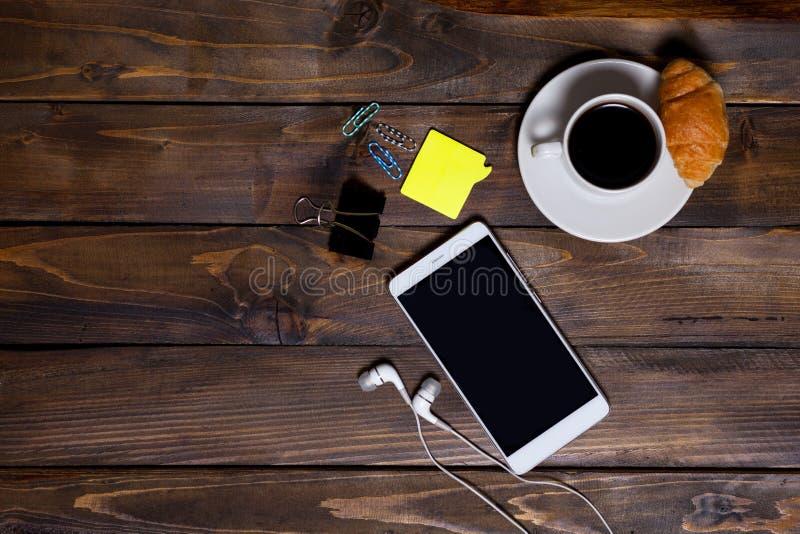 Weißer Handy auf hölzernem hölzernem Hintergrund mit Kopfhörer-, Tasse Kaffee-, Hörnchen- und Briefpapiergeräten lizenzfreies stockbild