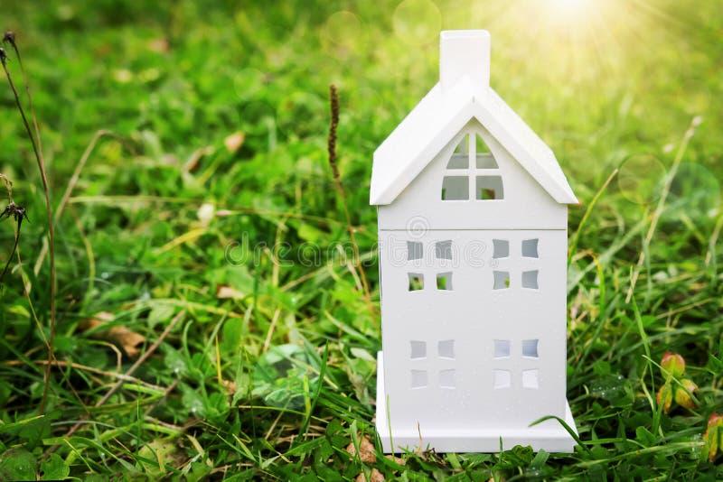 Weißer Hausplan auf grünem Gras Kleines Haus auf einem grünen backgr stockbilder