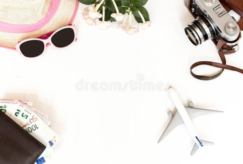 Weißer Hintergrund, Reise, Flugzeug, Kamera, Strohhut, Geldbeutel mit Bankkarten und Geld, Draufsicht lizenzfreies stockfoto