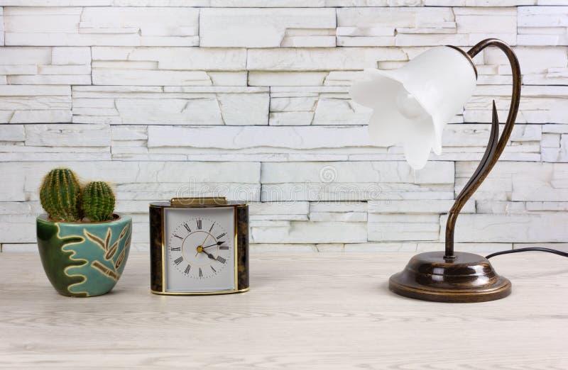 Weißer Holztisch mit einer Uhr eine Lampe und ein Kaktus lizenzfreies stockbild