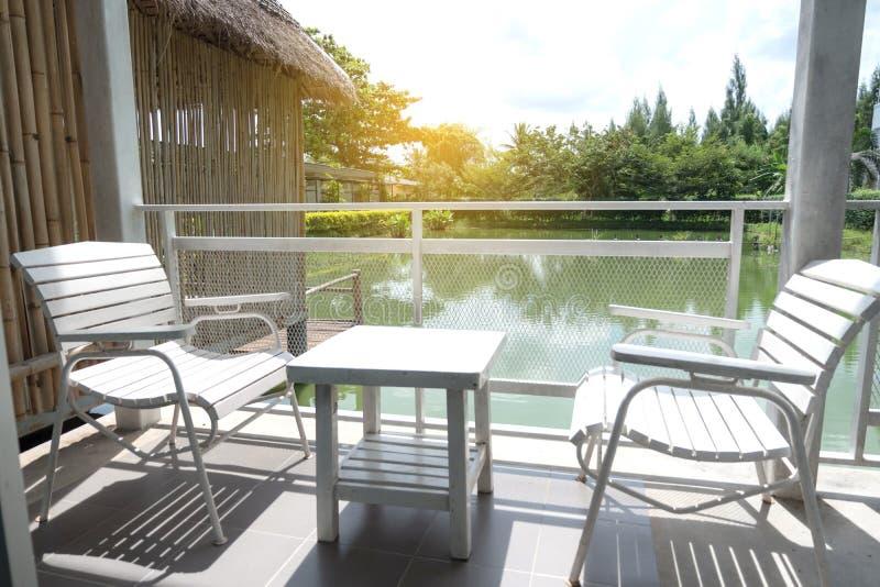 Weißer Holztisch und Stühle sind auf der Terrasse des Hauses lizenzfreie stockfotografie