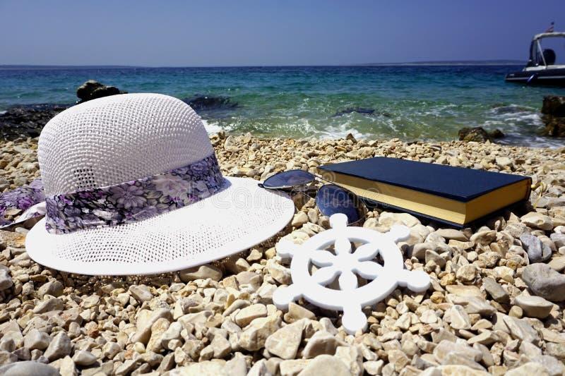 Weißer Hut, Sonnenbrille und Buch auf dem Pebble Beach fahren mit Meer und blauem Himmel im Hintergrund die Küste entlang Reisenk stockfotos