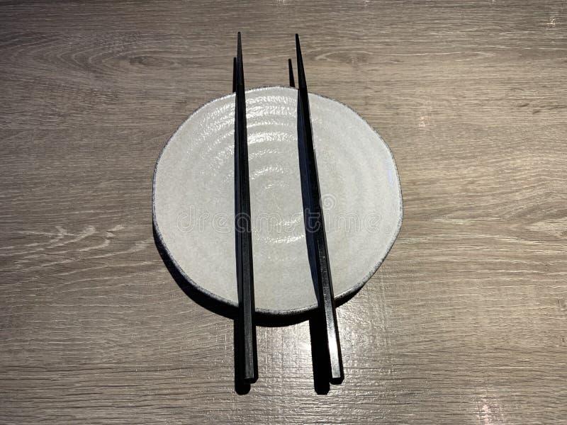 Weißer japanischer Teller mit Essstäbchen auf Holztisch stockbilder