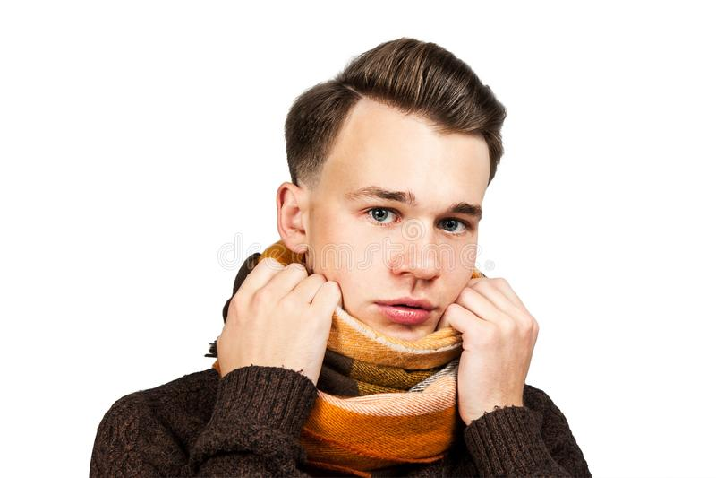 Weißer junger Kerl des Porträts, der sein Gesicht in der Strickjacke versteckt Getrennt auf einem weißen Hintergrund lizenzfreie stockfotografie