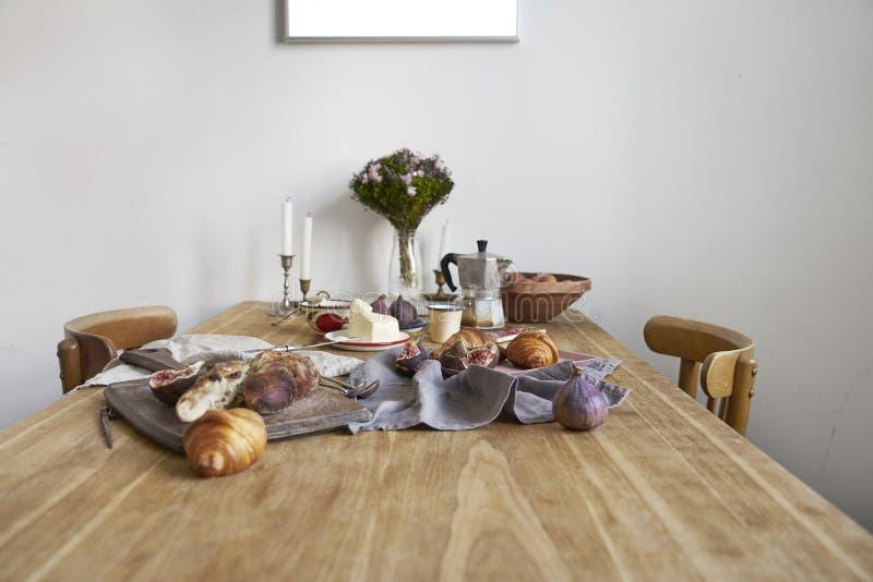 Weißer Kücheninnenraum mit Provence-Frühstück auf Holztisch, Plakat auf der weißen Wand, Raum für Entwurf stockbild