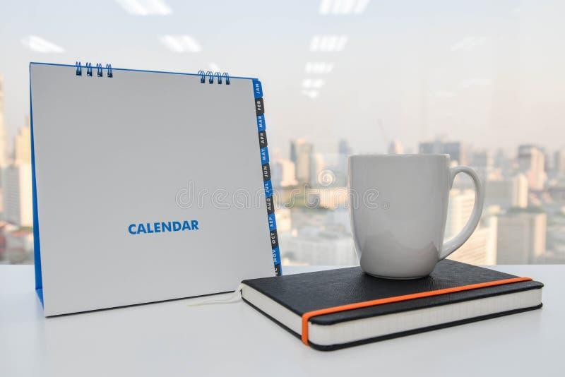 Weißer Kalender und ein Tasse Kaffee und ein Notizbuch stockbilder