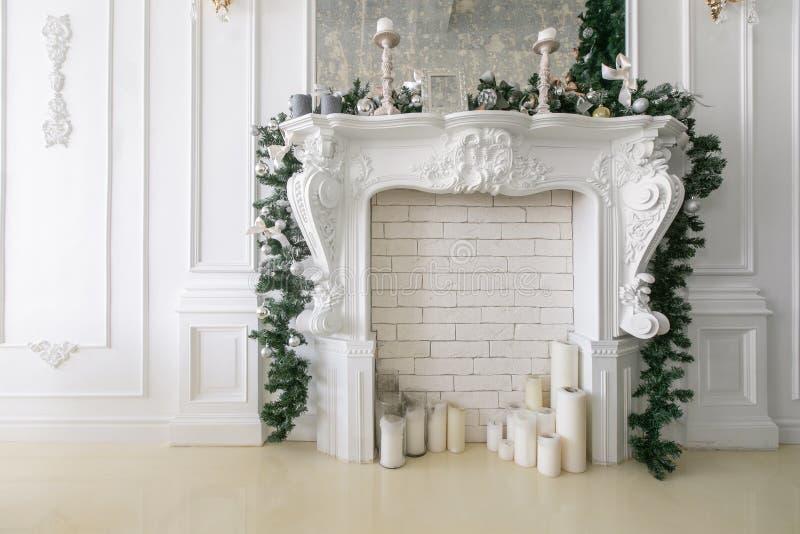 Weißer Kamin verziert mit Kerzen und Tannenzweigen Verzierter Weihnachtsbaum Klassische Wohnungen, Morgen im Hotel lizenzfreie stockfotos
