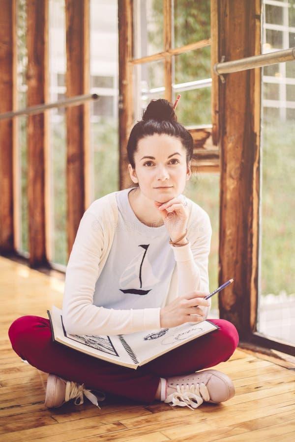 Weißer kaukasischer junger brunette weiblicher Künstler der Studentin, der auf Boden in der Collegeuniversität sitzt stockfotos