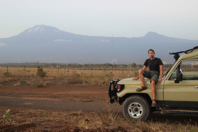 Weißer kaukasischer Reisender in der Sportkleidung sitzt in einem Jeep auf dem Hintergrund des Mount Kilimanjaros lizenzfreie stockfotografie