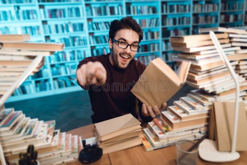 Weißer Kerl umgeben durch Bücher in der Bibliothek Student ist emotional Lesebuch stockfotografie