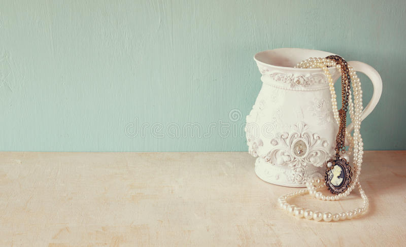 Weißer klassischer Victorianvase auf Holztisch mit einer Sammlung romantischem Weinleseschmuck und -perlen Retro- gefiltertes Bil lizenzfreie stockfotos