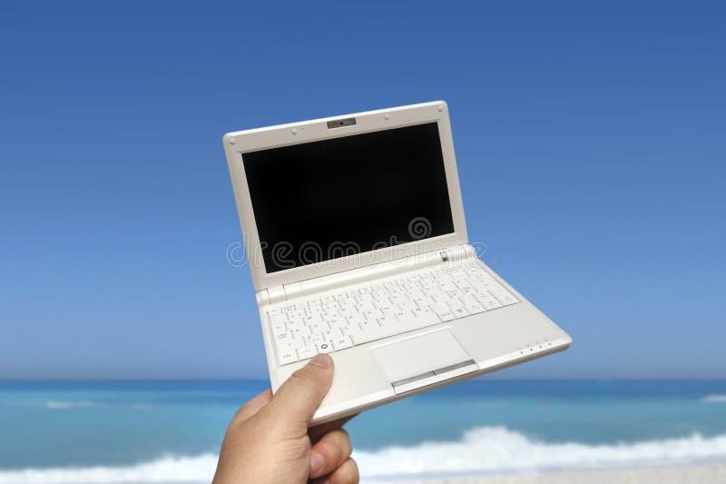 Weißer kleiner Laptop auf dem Strand lizenzfreies stockfoto