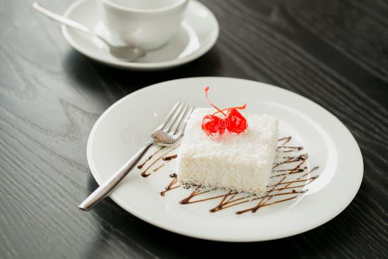Weißer Kuchen erstickte mit der Buttercreme und -kokosnüssen stockfotografie