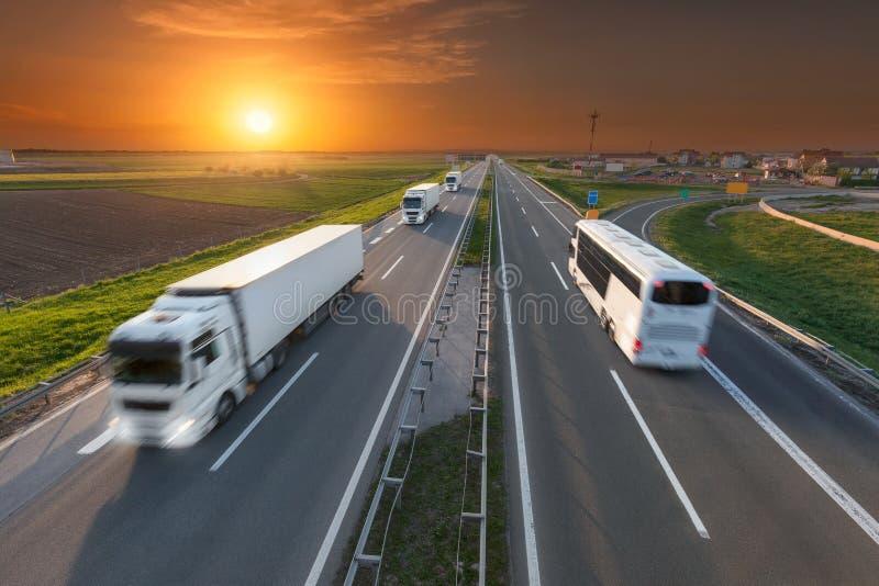 Weißer LKW und Bus in der Bewegungsunschärfe auf der Autobahn bei Sonnenuntergang stockfotos