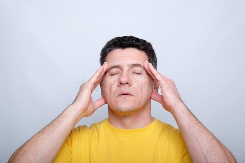 Weißer Mann von mittlerem Alter mit den geschlossenen Augen, die seinen Kopf mit zwei Händen berühren lizenzfreies stockfoto