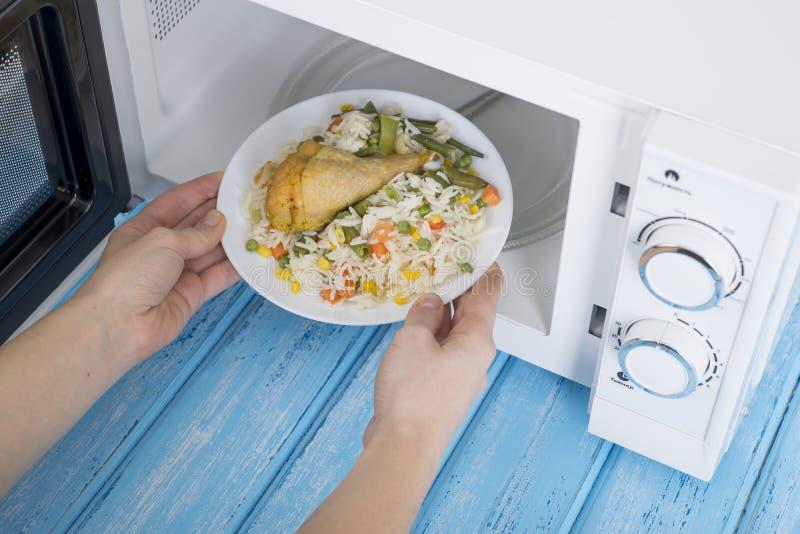 Weißer Mikrowellenherd, auf einer blauen Holzoberfläche für Heizungslebensmittel lizenzfreies stockbild