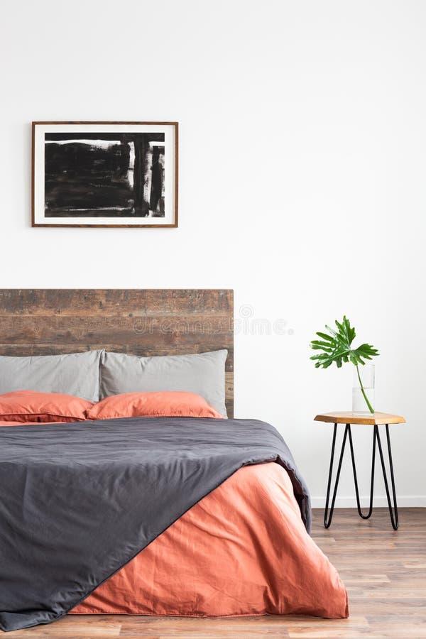 Weißer minimaler Innenraum mit einfachem Bett, korallenrote und graue Leinenbedsheets und nightstand lizenzfreie stockfotografie