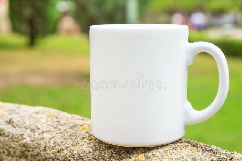 Weißer Modellkaffee oder Teebecher auf auf Stein draußen stehen Naturhintergrund mit grünem Baumgras Sommer-Frühling Leerstelle lizenzfreie stockfotografie