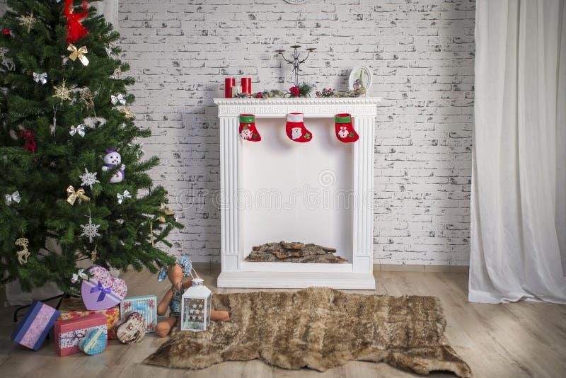 Weißer neues Jahr ` s Innenraum mit Kamin und grünem Baum stockfotos