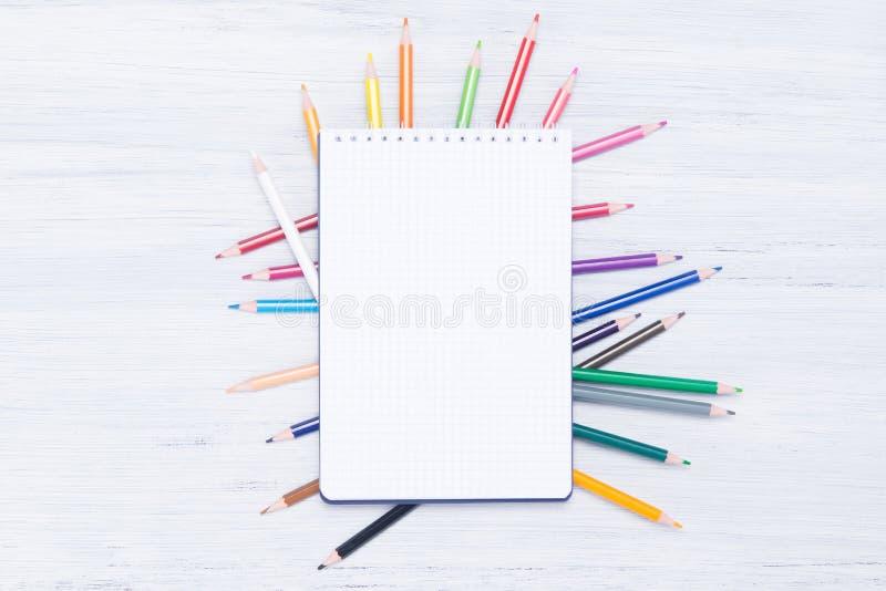 Weißer Notizblock für Anmerkungen, Lügen auf mehrfarbigen Bleistiften zerstreute auf ein Leuchtpult lizenzfreie stockbilder