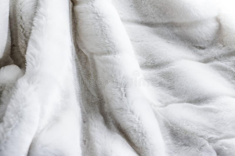 Weißer Pelzmantel-Beschaffenheitsluxushintergrund, künstliches Gewebedetail stockfoto