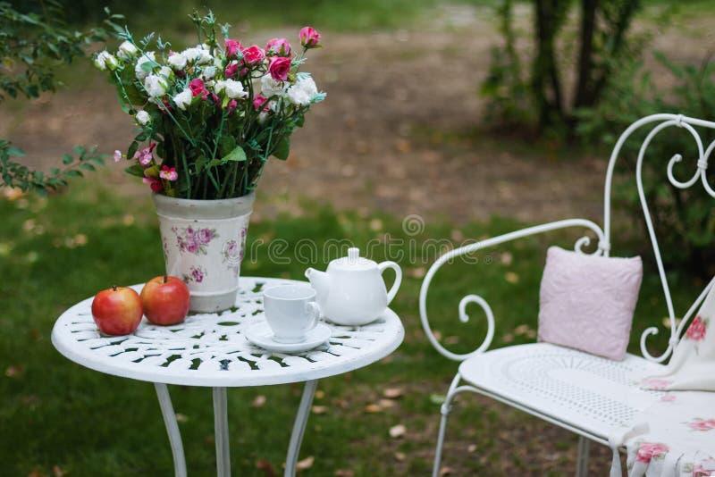 Weißer Porzellansatz für Tee oder Kaffee auf Tabelle im Garten über Unschärfegrün-Naturhintergrund Parteieinstellung des Sommers  stockfoto