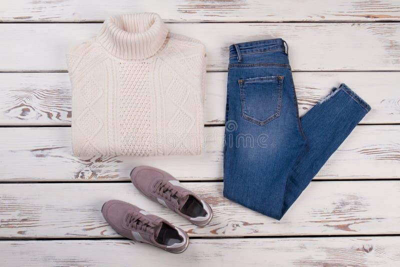 Weißer Pullover, Jeans und Turnschuhe lizenzfreies stockbild