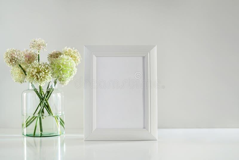 Weißer Rahmen auf einer Tischplatte und einem Knoblauch blüht Blumenstrauß, Front konkurrieren lizenzfreies stockbild