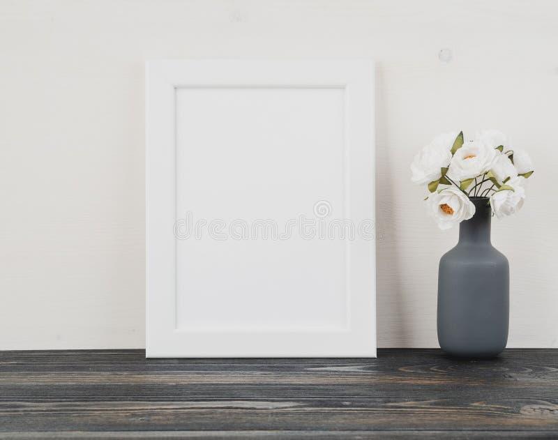 Weißer Rahmen, Blume im Vase, Uhr auf dunkelgrauem Holztisch aga lizenzfreie stockbilder