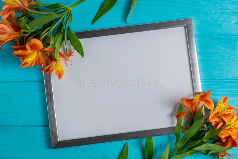 Weißer Rahmenspott oben mit Kopienraum für Text auf blauem hölzernem Hintergrund mit Alstroemeriablumen stockfotografie
