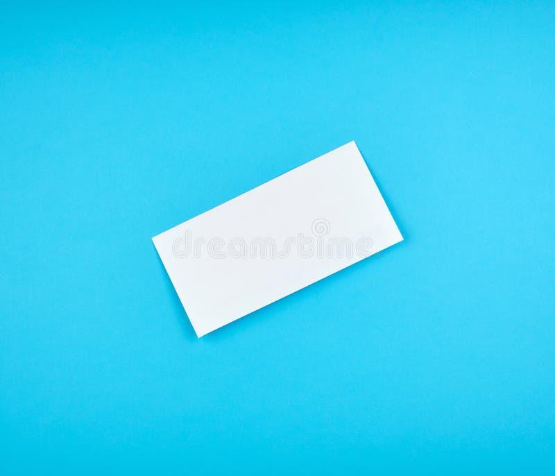 weißer rechteckiger Papierumschlag auf einem blauen Hintergrund stockfotos