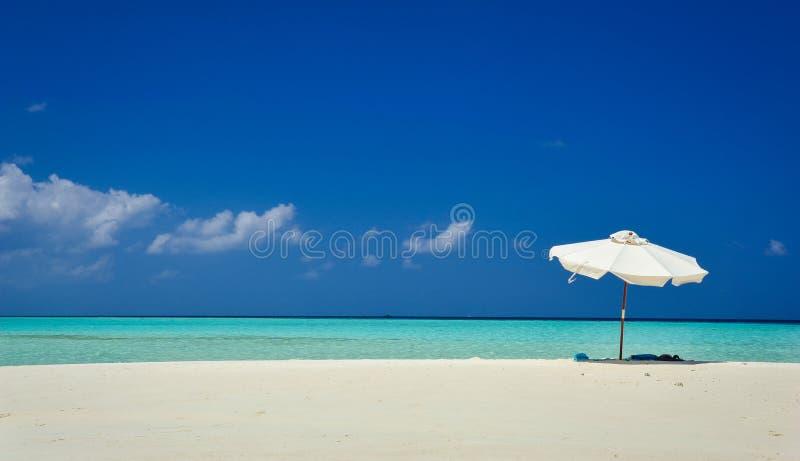Weißer Regenschirm auf idyllischem tropischem Sandstrand Weißer Strandschirm und blauer Himmel Sun und Regenschirm auf dem Strand lizenzfreie stockfotos
