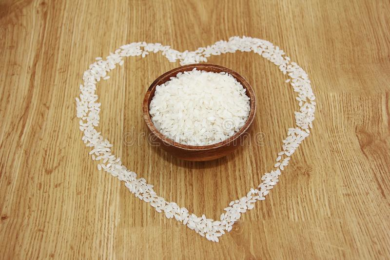 Weißer Reis in einem hölzernen Platten- und Reismuster in Form eines Herzens stockfoto