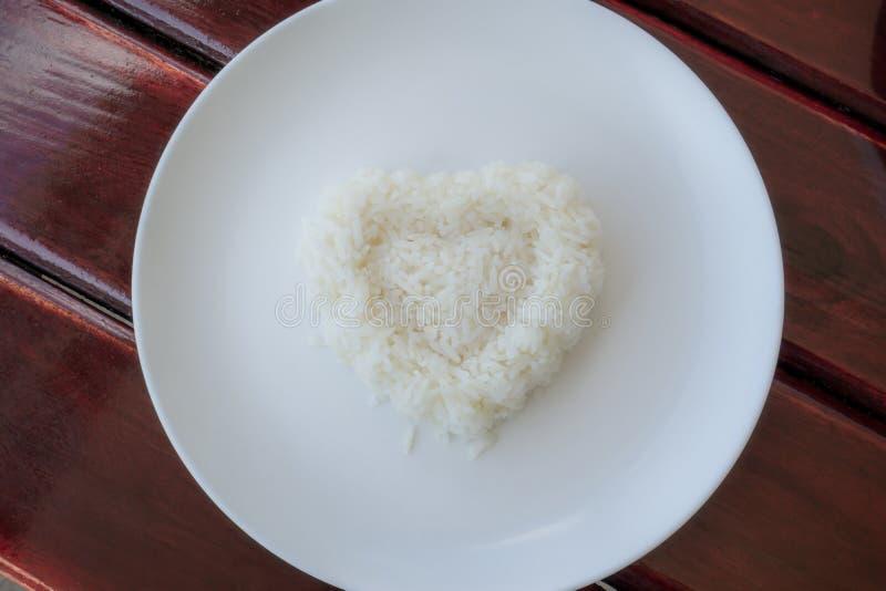 Wei?er Reis gekocht in der Herzform in einer wei?en Platte auf braunem Holztisch, Draufsichtfoto lizenzfreie stockfotos