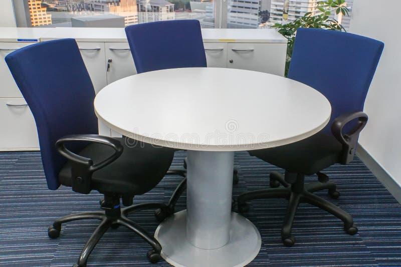 Weißer Rundtisch mit blauen Stühlen für Bürositzung stockfoto