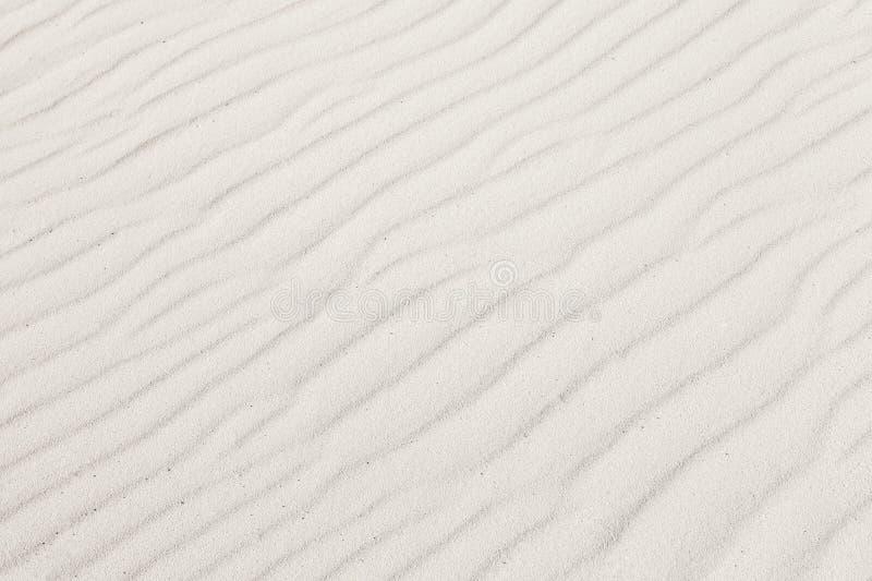 Weißer Sand mit Wellenhintergrundbeschaffenheit lizenzfreie stockfotos