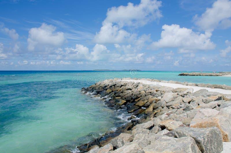 Weißer Sand und Steine des blauen Ozeans der Landschaftsmaledivischen Insel an Land stockfotografie